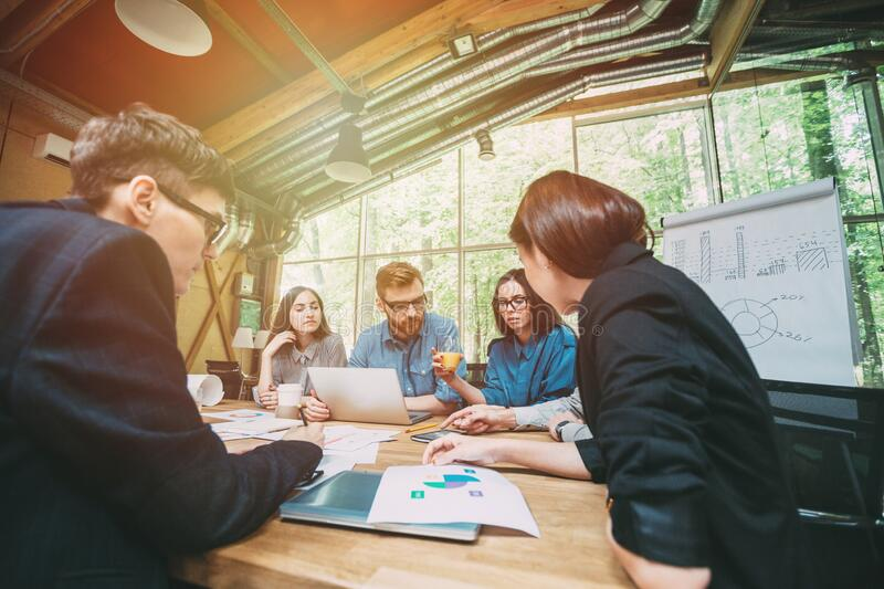 Creative team of professionals at the table meeting to discuss new ideas in modern startup office. Coworking royalty free stock photography