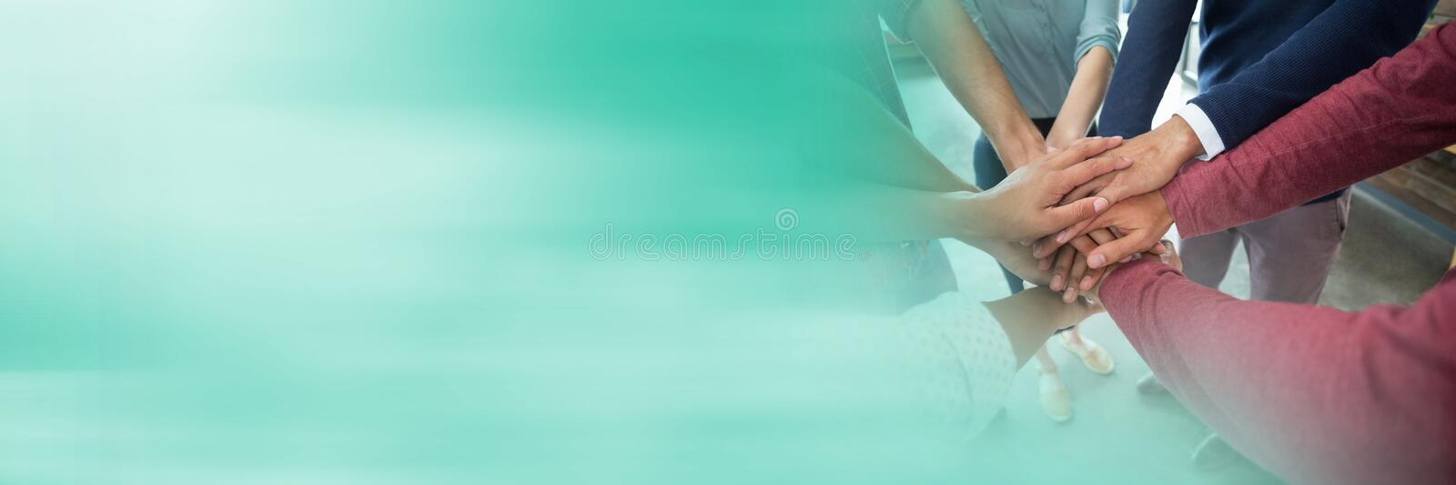 Creative team putting hands together and blurry teal transition stock images