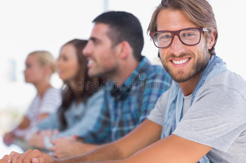 Creative team sitting in a line with one man smiling royalty free stock image