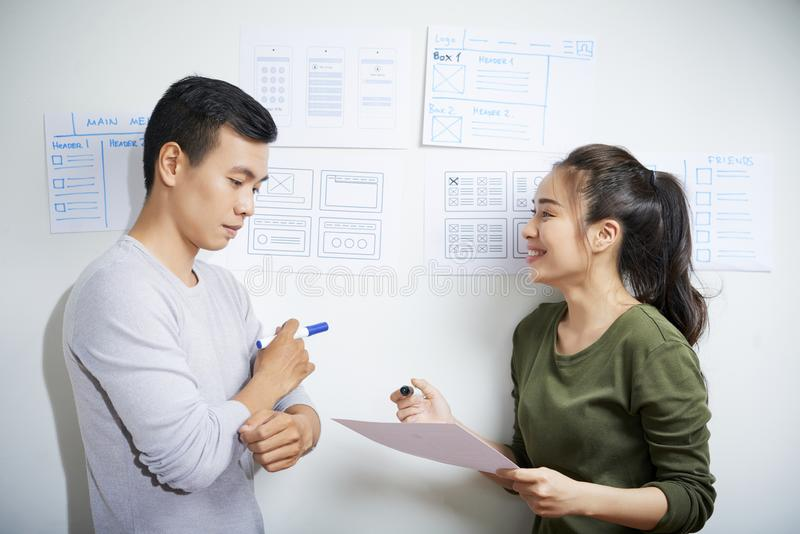 Creative team of user interface designers. Content creative Asian team of user interface designers standing near wall with attached drawings and discussing ideas stock image