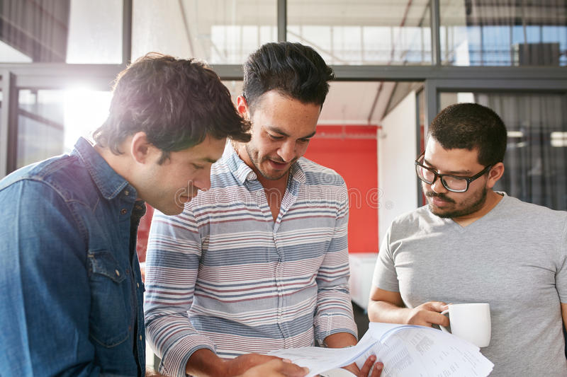 Creative team working on their business project. Together at office. Three young men looking at some documents in a small meeting stock photos