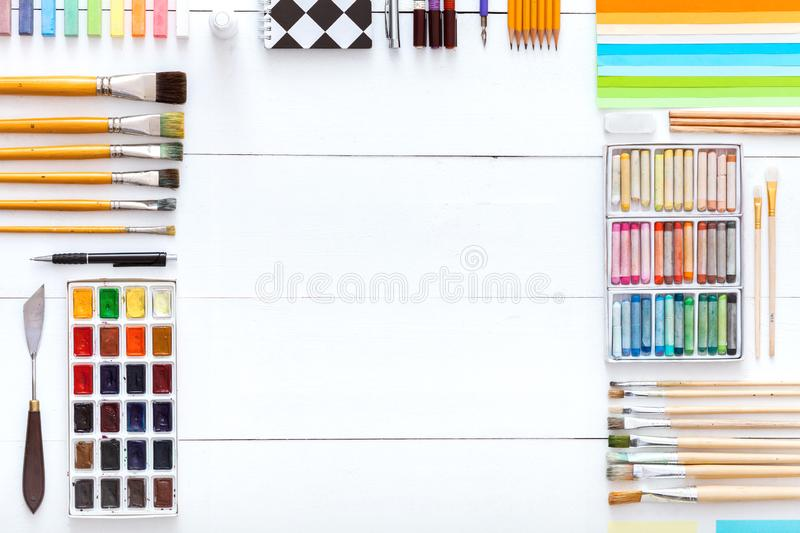 Creative tools desk with drawing painting supplies, colorful paints brushes pencils crayons and school accessories set for art. Work on white wooden table stock photos