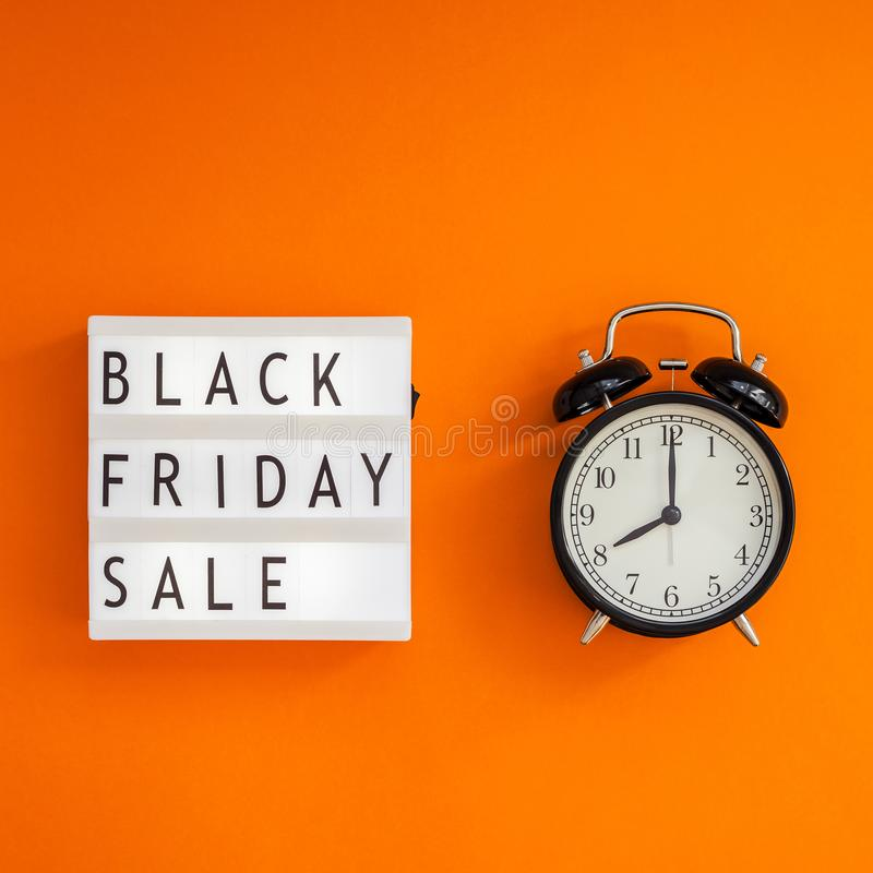 Creative Top view flat lay promotion composition Black friday sale text on lightbox alarm clock orange background copy space. Square Template Black friday sale stock images