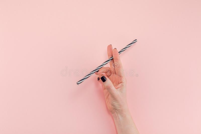 Woman hand with cocktail drinking straw. Creative top view flat lay of woman hand with black manicure holding cocktail drinking straw like cigarette with copy royalty free stock photo