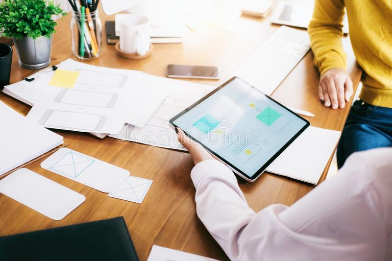 UX UI designer team meeting to design mobile application. Creative UX UI designer teamwork meeting and planning to design the user interface wireframe layout of royalty free stock photo