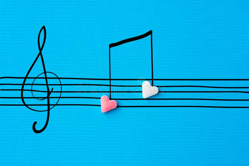 Creative Valentine greeting card. Sugar heart shape candies hand drawn doodle sketch musical notes on staff treble clef on blue stock photography