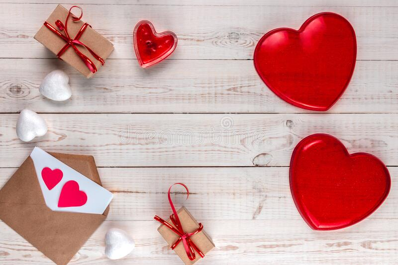 Creative valentine`s day composition, white wooden background with gifts, red hearts, candle, envelope, valentines day concept, royalty free stock photos