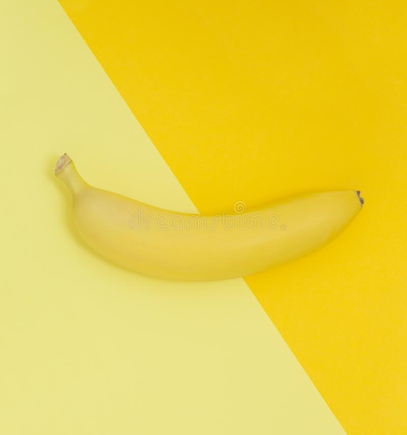 Creative view of a banana on a background of similar colors. Yellow background. stock photos