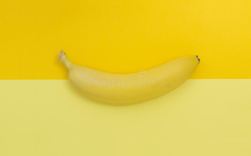 Creative view of a banana on a background of similar colors. Yellow background. stock photo