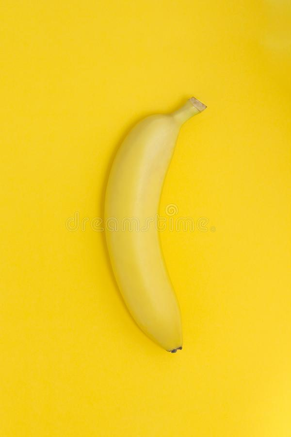 Creative view of a banana on a paper yellow background. Similar colors royalty free stock images