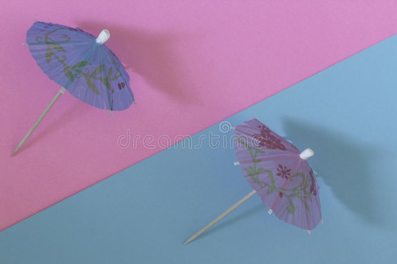 Creative view of a cocktail umbrella on a two-tone background -. Pink and blue. Conceptual image of summer. Minimalism. Summertime. Top view stock image