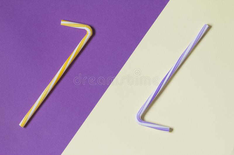Creative view of drinking straws for party on a two-tone background - ultra violet and yellow. Complementary colors. Creative view of drinking straws for party royalty free stock images