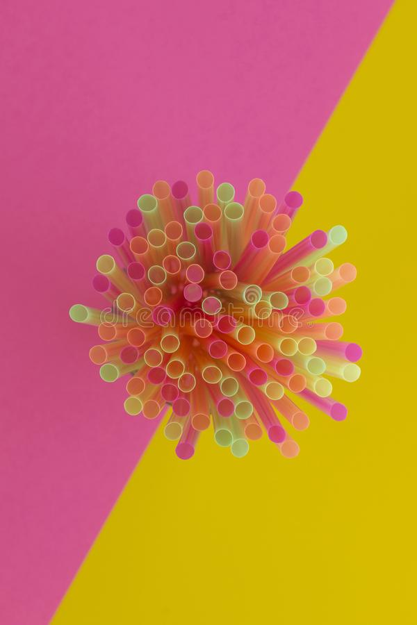 Creative view of drinking strawsneon colors party on a two-ton. E background - pink and yellow. Top view stock photo