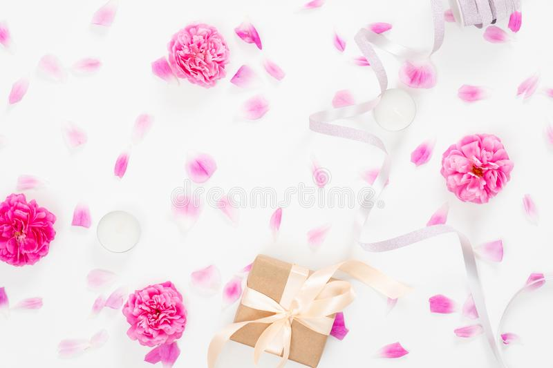 Creative wedding composition with pink rose flower buds, petals, ribbon, gift box on white background. Minimal flat lay style royalty free stock images