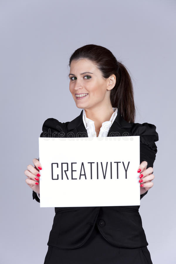 Creative woman. Happy businesswoman showing a paper with the word creativity royalty free stock image