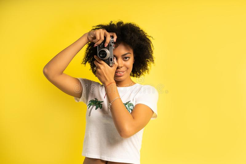 Creative woman-photographer takes photos, isolated on yellow. royalty free stock images