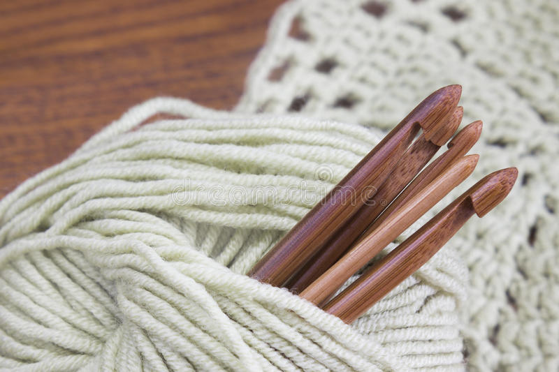 Creative work place for homemade crafts. Wooden natural bamboo crochet hooks, doily and yarn ball on the table. Creative work place for homemade crafts. Wooden royalty free stock photography