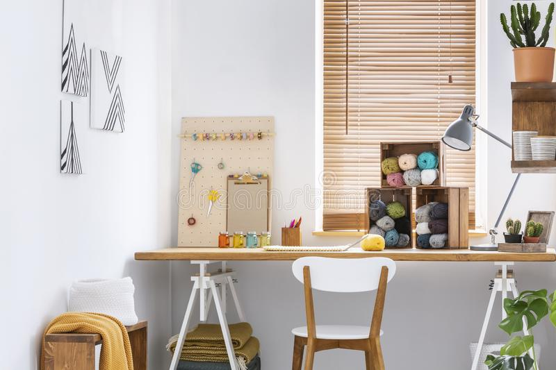 Creative workspace with scandinavian, wooden furniture, white walls and sewing tools in a modern crafts room interior. Real photo. stock images