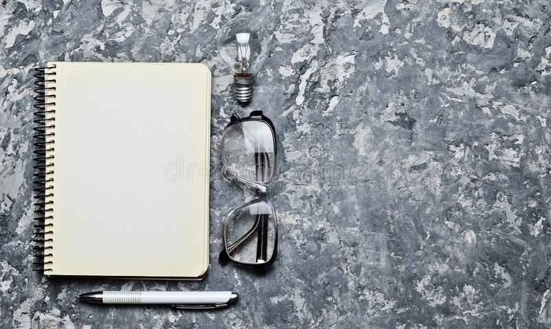 The creative workspace of the writer is inspiring to create. I have an idea. Notepad, pen, incandescent bulb, glasses. On a concrete table. Top view. Flat lay stock images