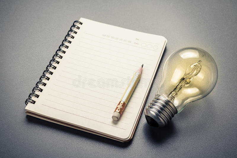 Creative Writing. Pencil on notebook with glowing light bulb stock photography
