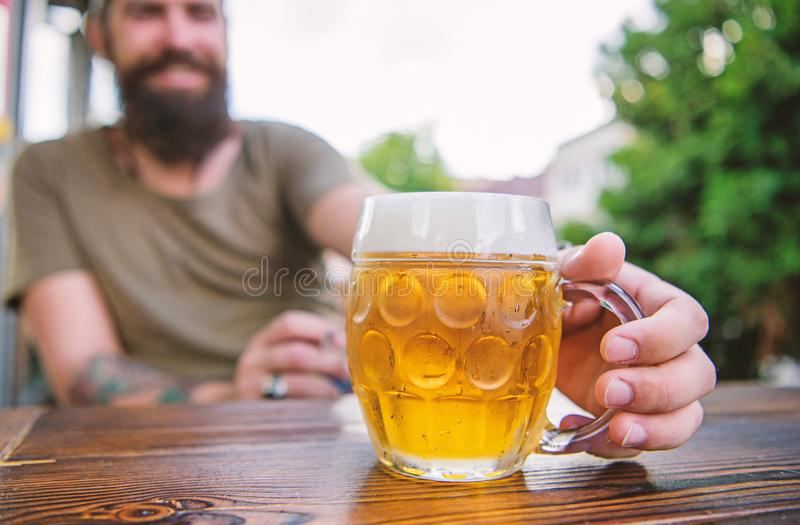 Creative young brewer. Craft beer is young, urban and fashionable. Distinct beer culture. Mug cold fresh beer on table. Close up. Man sit cafe terrace enjoying stock photography