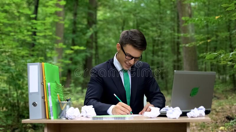 Creative young businessman writing down good ideas at desk in green forest stock photos