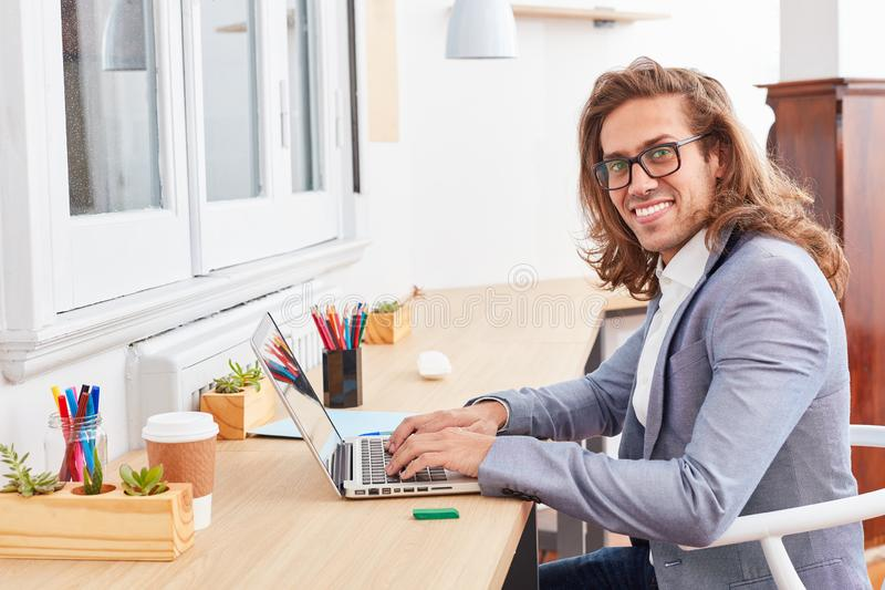 Creative young man as a nerd at the laptop. Creative young business man as nerd or founder at laptop computer in office stock photo