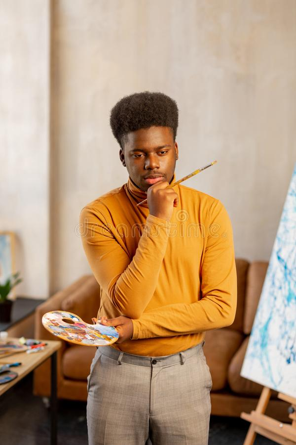 Creative young man thinking about his painting stock photos