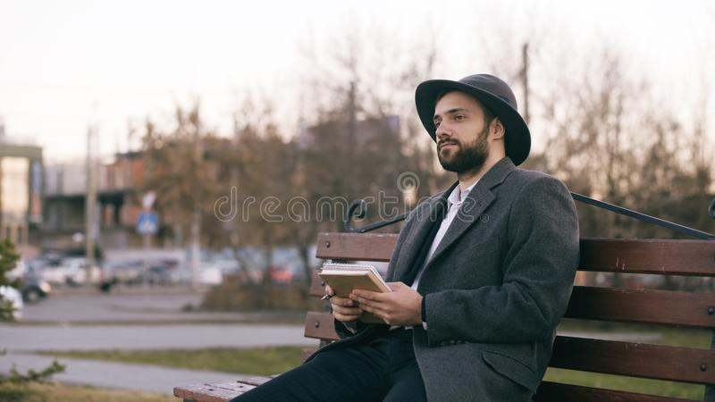 Creative young writer man in hat and coat write notes for his future book with pen in notebook sitting on city street royalty free stock image