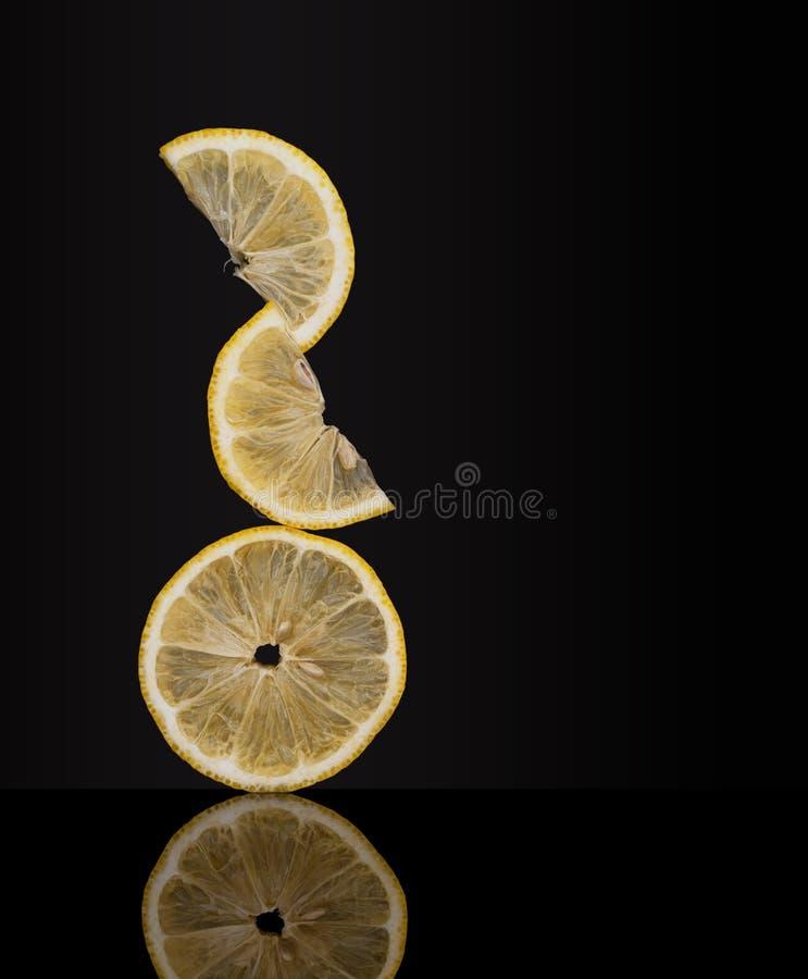 Creatively allsidiga nya citronfruktskivor på mörk bakgrund ovanligt foto Verka för att trotsa gravitation royaltyfri fotografi