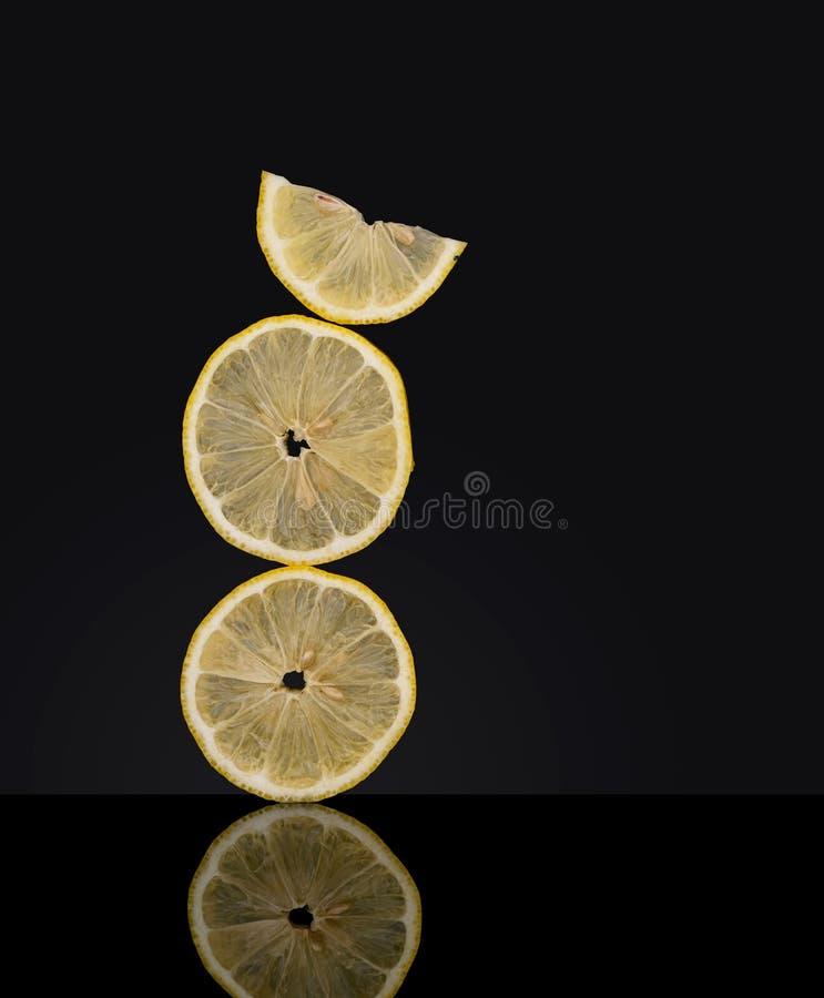 Creatively allsidiga nya citronfruktskivor på mörk bakgrund ovanligt foto Verka för att trotsa gravitation royaltyfria bilder