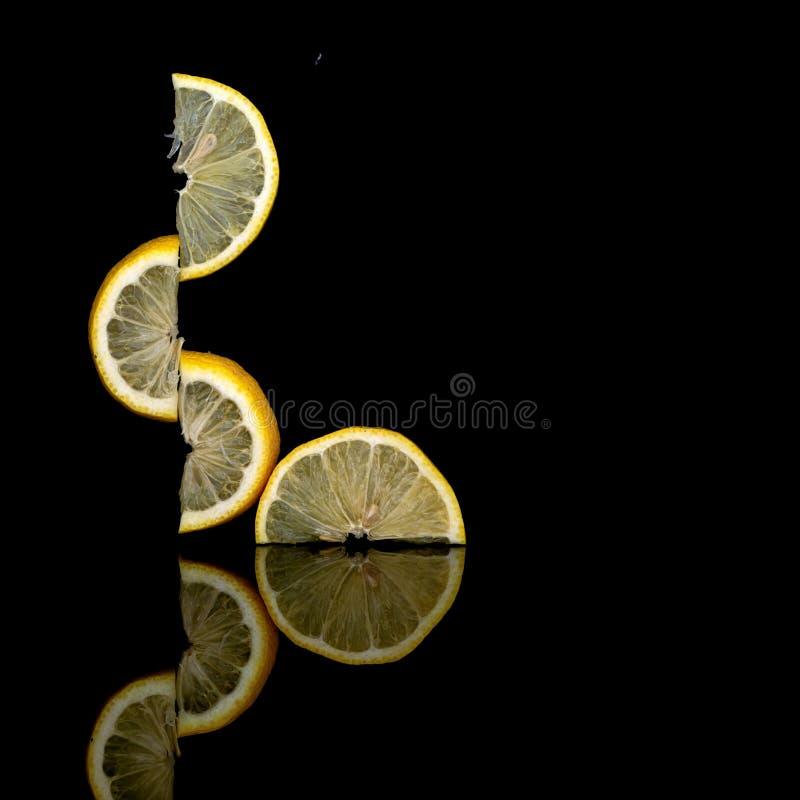 Creatively allsidiga nya citronfruktskivor på mörk bakgrund ovanligt foto Verka för att trotsa gravitation Isolerat på svart royaltyfri foto