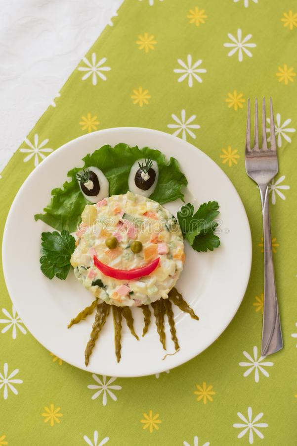 Creatively decorated octopus salad. Children`s menu on a green background stock images