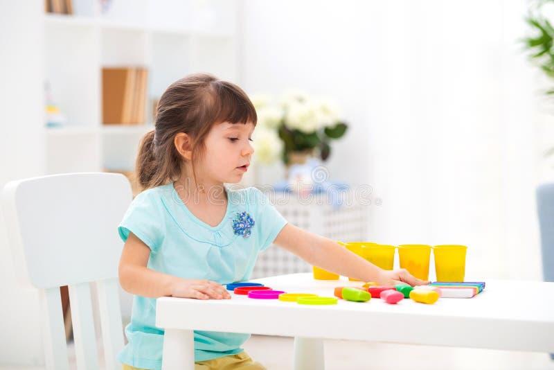 Creatividad de los niños El niño esculpe de la arcilla La niña linda moldea del plasticine en la tabla en sitio imagen de archivo libre de regalías