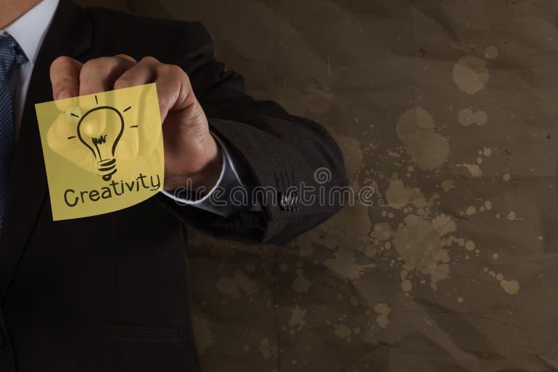 Creatività di tiraggio della mano dell'uomo d'affari sulla nota appiccicosa con il crum della spruzzata fotografie stock libere da diritti