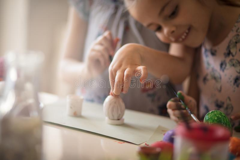 Creativity all around. Little girls coloring Easter egg royalty free stock images