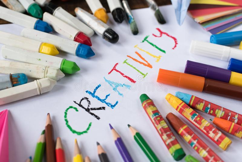 Creativity concept - colorful paper, crayon, colorful pencil and paper with word CREATIVITY royalty free stock image