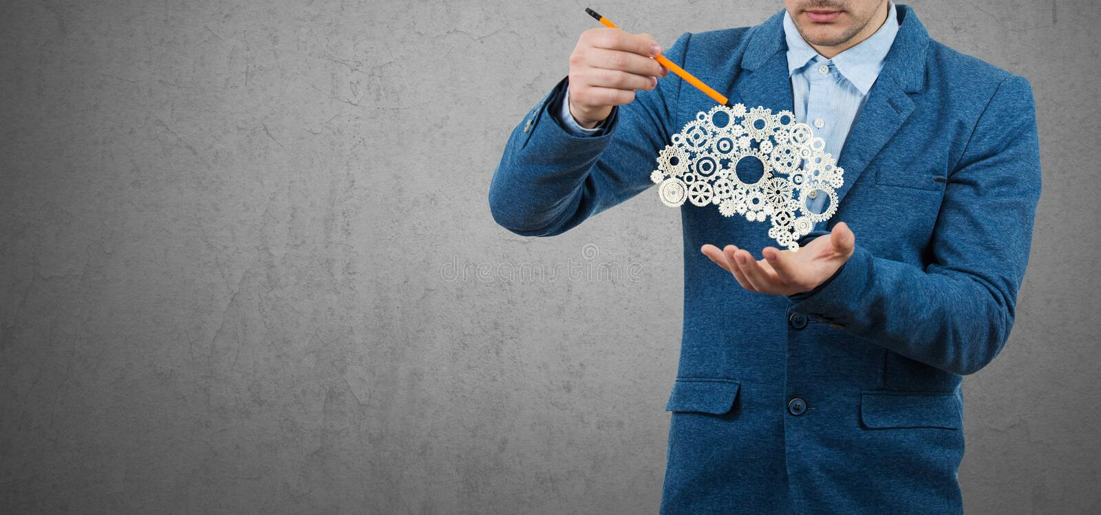 Creativity concept. Creative businessman holding a pencil in his hand try to draw an imaginary brain made from gears. Grey wall background.Creativity Concept stock photo