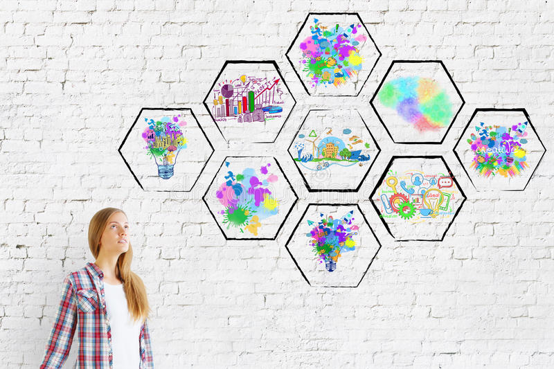 Creativity concept. Thoughtful young european girl on brick background with abstract colorful drawings inside cells. Creativity concept royalty free stock image