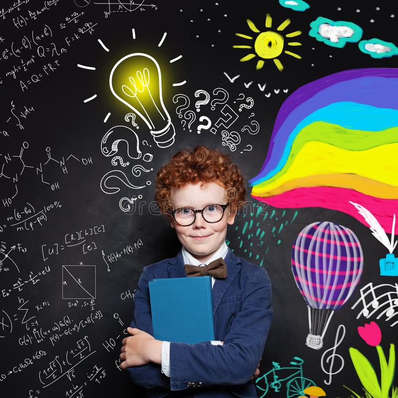 Creativity education. Clever child boy in suit and glasses holding textbook on science and arts occupations pattern background royalty free stock photos