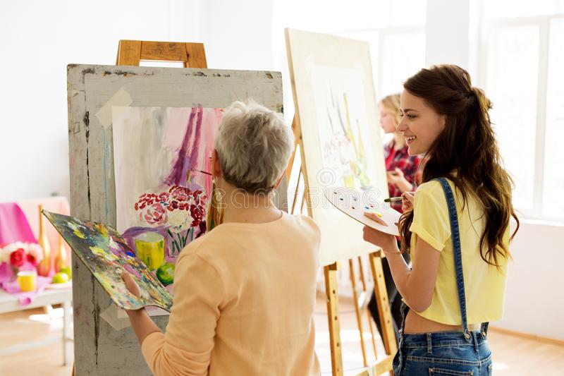 Happy women painting at art school studio. Creativity, education and people concept - happy women with brushes and palettes painting still life picture on easel royalty free stock images