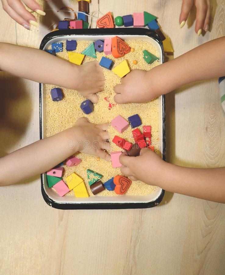 Children playing with kinetic sand, croup and designer in preschool. The development of fine motor concept. Creativity Game. Creativity Game concept. Children stock photos