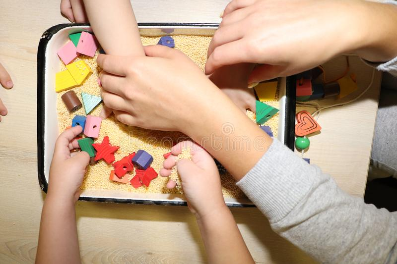 Children playing with kinetic sand, croup and designer in preschool. The development of fine motor concept. Creativity Game. Creativity Game concept. Children stock photo