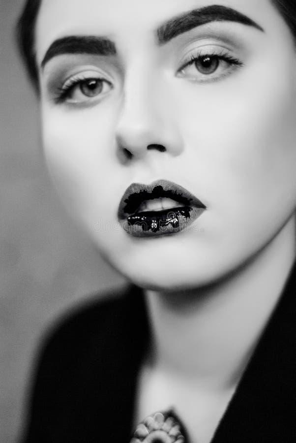 Creativo componga de labios líquidos negros en cierre encima de la foto blanco y negro La creatividad adentro en etapa compone fotos de archivo