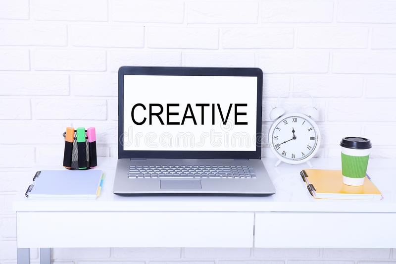 creativo Texto no monitor Local de trabalho moderno com computador, xícara de café e pulso de disparo Zombaria ascendente e espaç imagens de stock