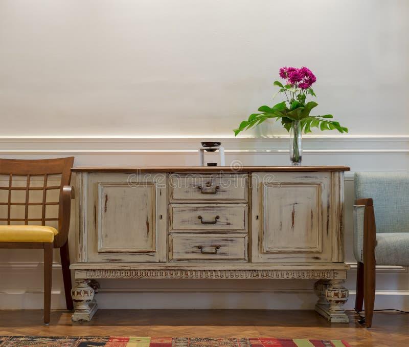 Credenza d'annata di legno del bianco sporco, vaso di vetro con i fiori rossi, due sedie sulla parete bianca e pavimento di parqu immagine stock