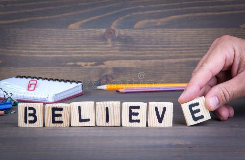 Credi dalle lettere di legno su fondo di legno immagini stock