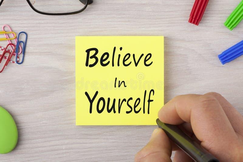 Credi in voi stesso la scrittura sulla nota fotografia stock