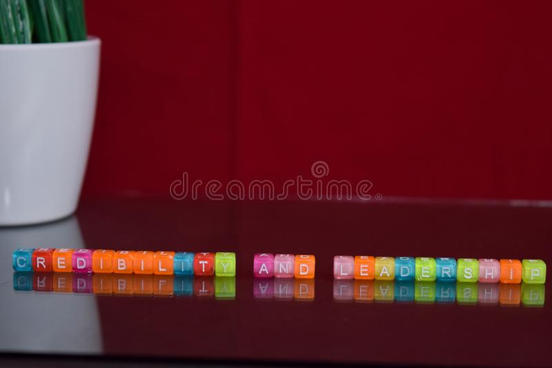 Credibility and leadership text at colorful wooden block on red background. Desk office and education concept stock photography