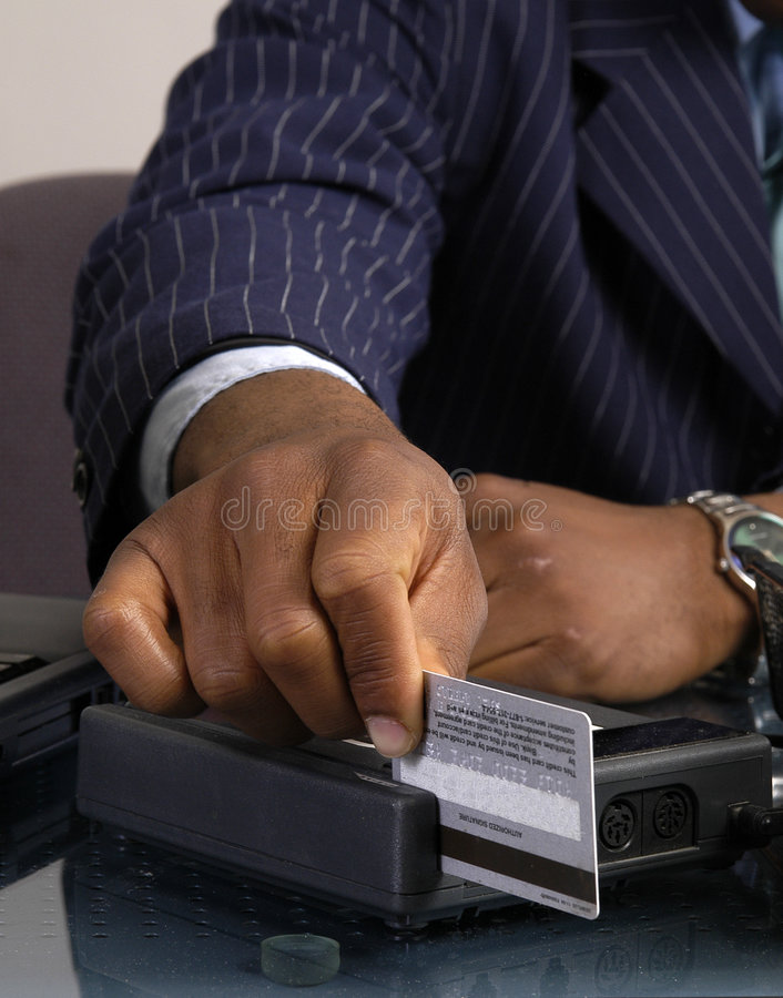 Credit Card. A man swipes a credit card through the terminal stock photography